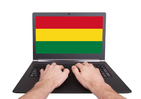 Hands working on laptop showing on the screen the flag of Bolivia photo