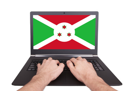 Hands working on laptop showing on the screen the flag of Burundi photo