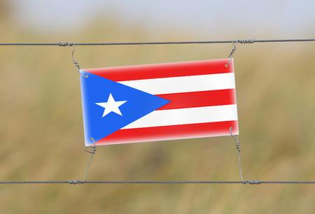 bandera de puerto rico: Cerca de la frontera - cartel de pl�stico viejo con una bandera - Puerto Rico