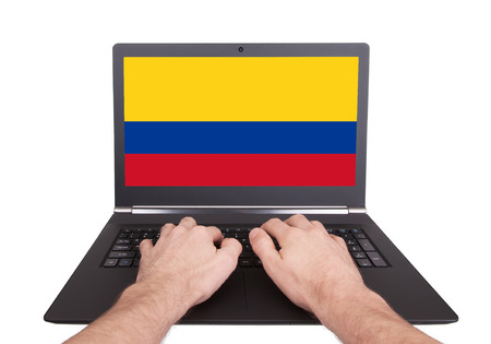 Hands working on laptop showing on the screen the flag of Colombia photo