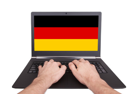 electronic voting: Hands working on laptop showing on the screen the flag of Germany Stock Photo