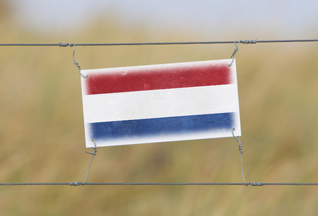 Border fence - Old plastic sign with a flag - Netherlands photo