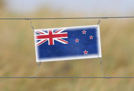 bandera de nueva zelanda: Cerca de la frontera - cartel de pl�stico viejo con una bandera - Nueva Zelanda