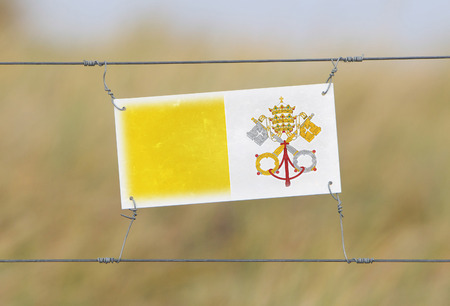 vatican city: Border fence - Old plastic sign with a flag - Vatican City
