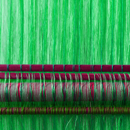 textile industry: Handmade silk textile industry, silk scarf on a old machine (Vietnam), green Stock Photo