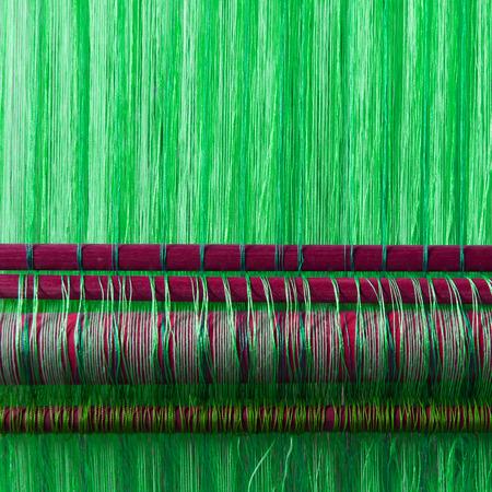 industria textil: Hecho a mano industria textil de seda, bufanda de seda en una vieja m�quina (Vietnam), verde