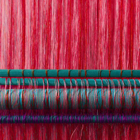 textile industry: Handmade silk textile industry, silk scarf on a old machine (Vietnam), red Stock Photo
