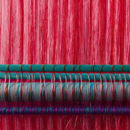 industria textil: Hecho a mano industria textil de seda, bufanda de seda en una vieja m�quina (Vietnam), rojo