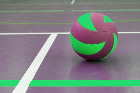 Green and purple ball on court at break time, school gym