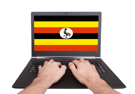 electronic voting: Hands working on laptop showing on the screen the flag of Uganda Stock Photo