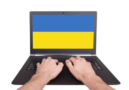 Hands working on laptop showing on the screen the flag of Ukraine photo