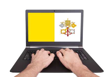 Hands working on laptop showing on the screen the flag of Vatican City photo