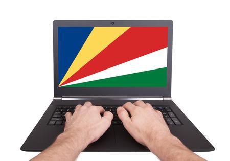 Handen die op laptop werken die op het scherm de vlag van de Seychellen tonen