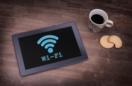 Tablet with Wi-Fi connection on a wooden desk,vintage setting photo