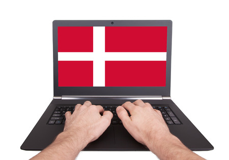 Hands working on laptop showing on the screen the flag of Denmark photo
