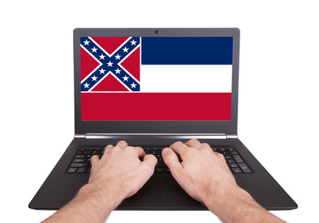Hands working on laptop showing on the screen the flag of Mississippi photo