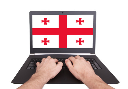 Hands working on laptop showing on the screen the flag of Georgia photo