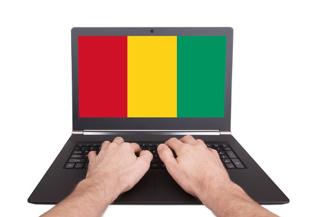 electronic voting: Hands working on laptop showing on the screen the flag of Guinea