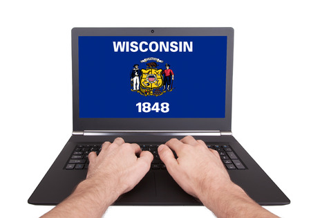 Hands working on laptop showing on the screen the flag of Wisconsin photo