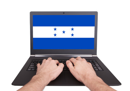 Hands working on laptop showing on the screen the flag of Honduras photo