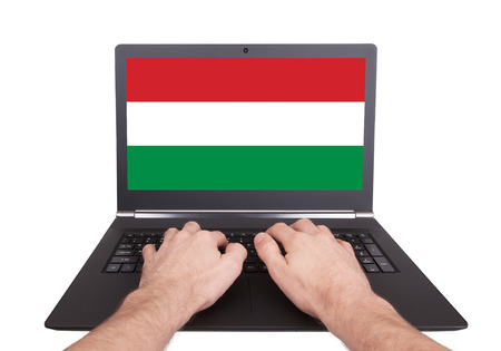 electronic voting: Hands working on laptop showing on the screen the flag of Hungary