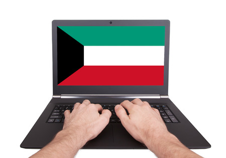 Hands working on laptop showing on the screen the flag of Kuwait photo
