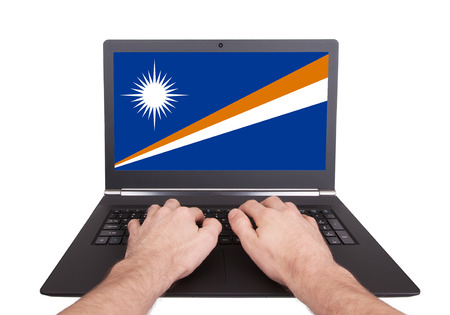 electronic voting: Hands working on laptop showing on the screen the flag of Marshall Islands