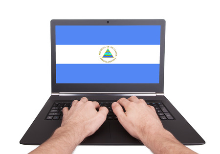 electronic voting: Hands working on laptop showing on the screen the flag of Nicaragua Stock Photo