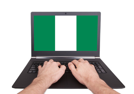 Hands working on laptop showing on the screen the flag of Nigeria photo