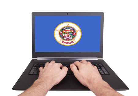 Hands working on laptop showing on the screen the flag of Minnesota photo