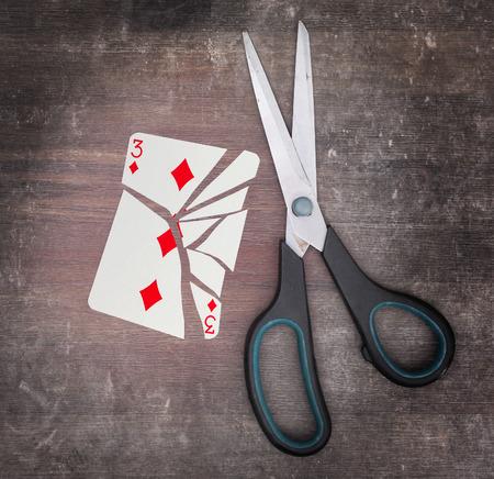 doublet: Concept of addiction, card with scissors, three of diamond Stock Photo