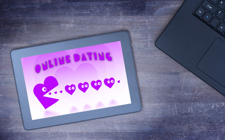 pacman: Online dating on a tablet - concept of love, purple pacman eating hearts