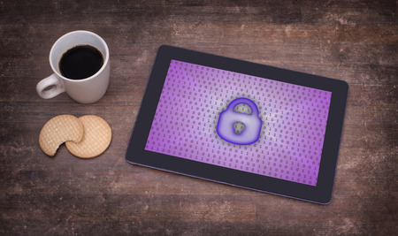 Tablet on a desk, concept of data protection, purple photo