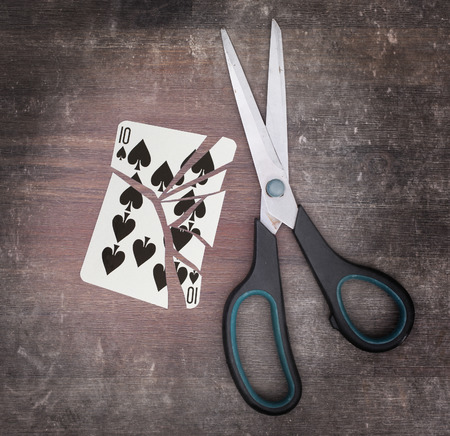 doublet: Concept of addiction, card with scissors, ten of spades