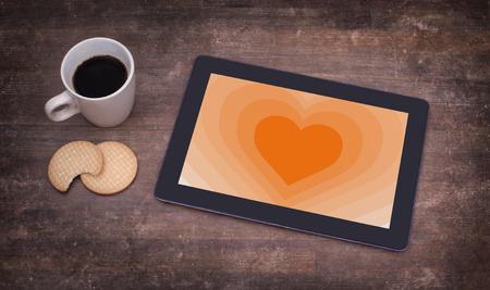 communicator: Heart shape backgound on a tablet - Concept of love - orange Stock Photo