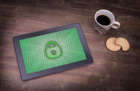 Tablet on a desk, concept of data protection, green photo