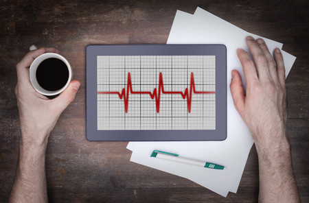 heart ekg trace: Electrocardiogram on a tablet - Concept of healthcare, heartbeat shown on monitor - red