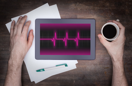 sine wave: Electrocardiogram on a tablet - Concept of healthcare, heartbeat shown on monitor - pink Stock Photo