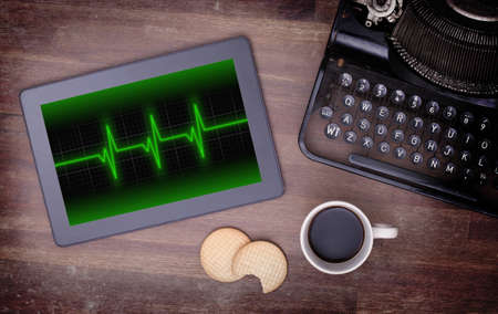 heart ekg trace: Electrocardiogram on a tablet - Concept of healthcare, heartbeat shown on monitor - green Stock Photo