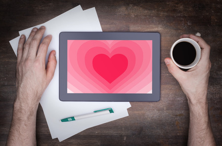 Heart shape backgound on a tablet - Concept of love - pink photo