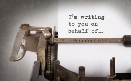 behalf: Close-up of a vintage typewriter, old and rusty, Im writing to you on behalf of