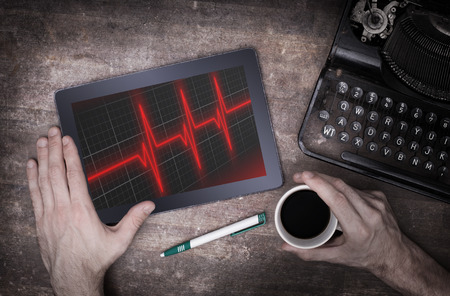heart ecg trace: Electrocardiogram on a tablet - Concept of healthcare, heartbeat shown on monitor - red