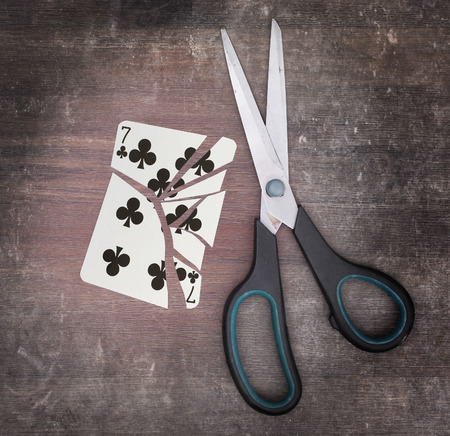 doublet: Concept of addiction, card with scissors, seven of clubs