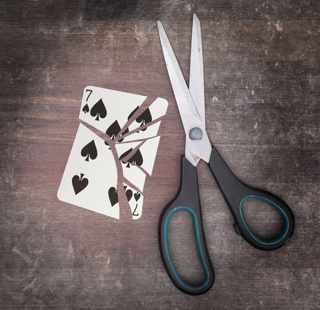 doublet: Concept of addiction, card with scissors, seven of spades Stock Photo