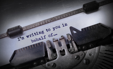 behalf: Vintage inscription made by old typewriter, Im writing to you in behalf of Stock Photo