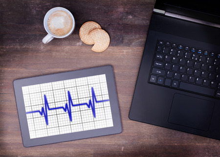 heart ekg trace: Electrocardiogram on a tablet - Concept of healthcare, heartbeat shown on monitor - blue