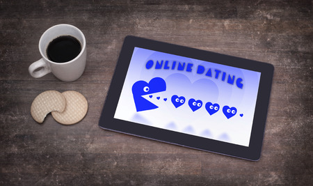 pacman: Online dating on a tablet - concept of love, blue pacman eating hearts