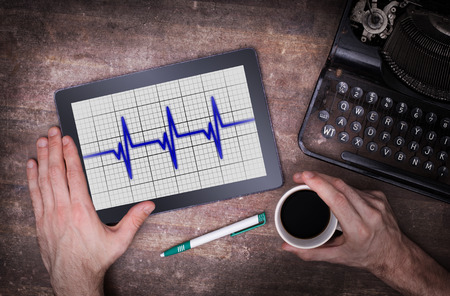 heart ecg trace: Electrocardiogram on a tablet - Concept of healthcare, heartbeat shown on monitor - blue