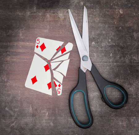 doublet: Concept of addiction, card with scissors, five of diamond Stock Photo