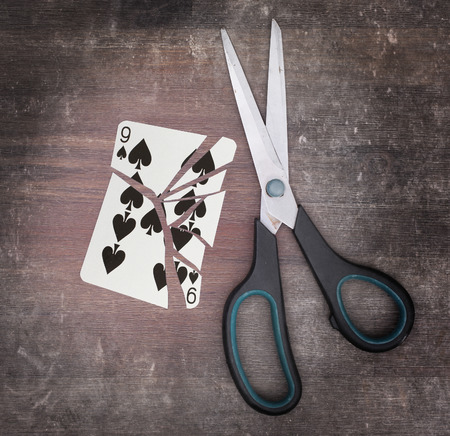 Concept of addiction, card with scissors, nine of spades photo